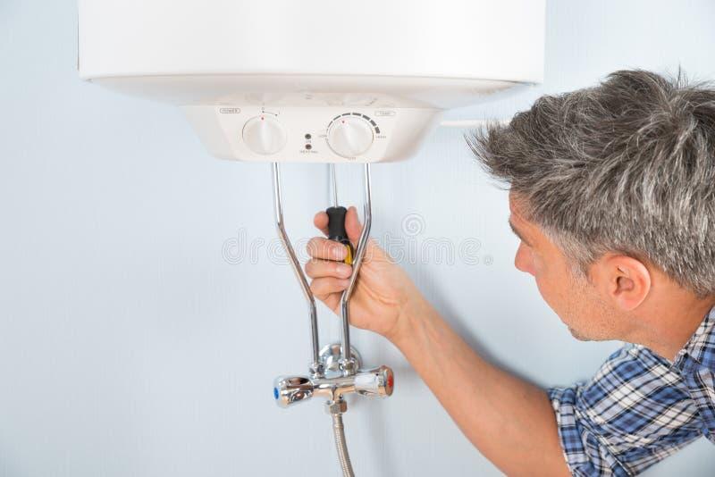 Fontanero que repara el calentador de agua fotografía de archivo libre de regalías