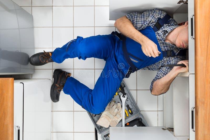 Fontanero que repara el fregadero fotos de archivo