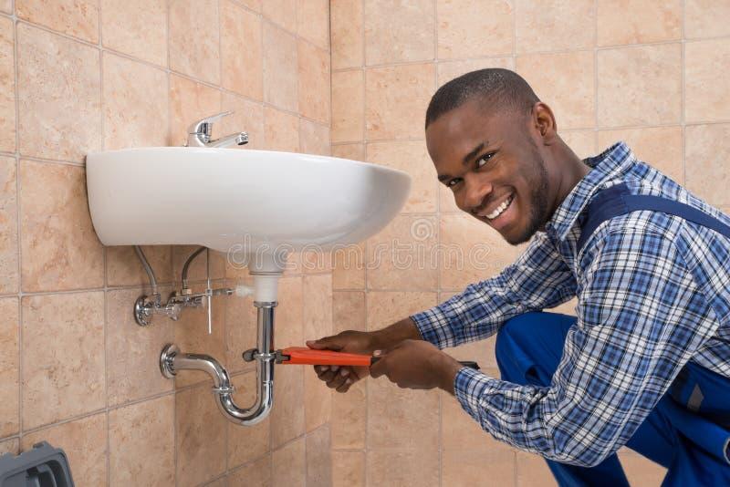 Fontanero que repara el fregadero en cuarto de baño foto de archivo