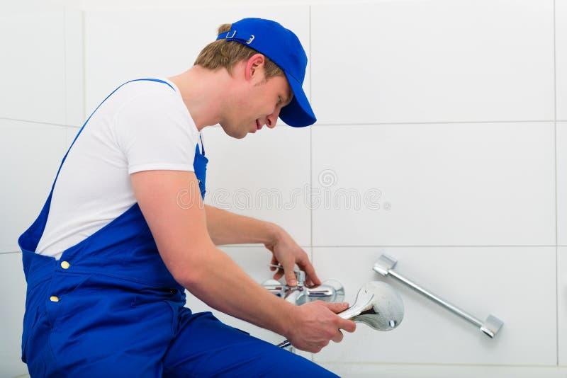 Fontanero que repara la ducha en sitio del baño fotos de archivo