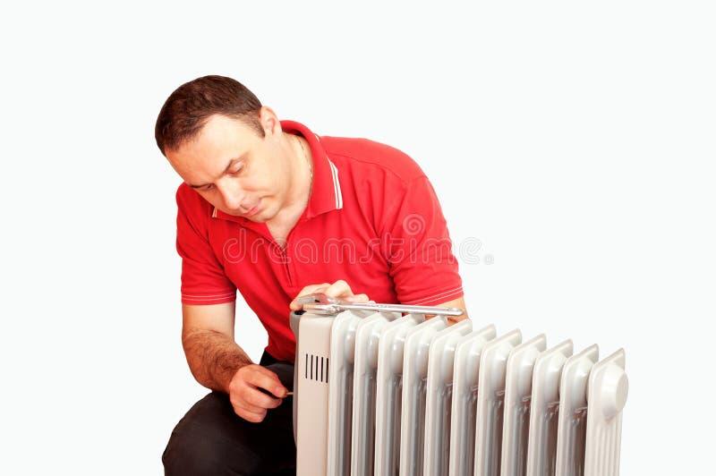 Fontanero que repara un calentador foto de archivo libre de regalías