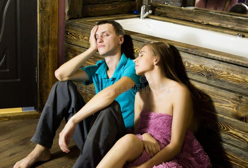 Fontanero que tiene el ligón con la chica joven en casa hombres que localizan en una bañera del piso, cansada y soñolienta despué imágenes de archivo libres de regalías