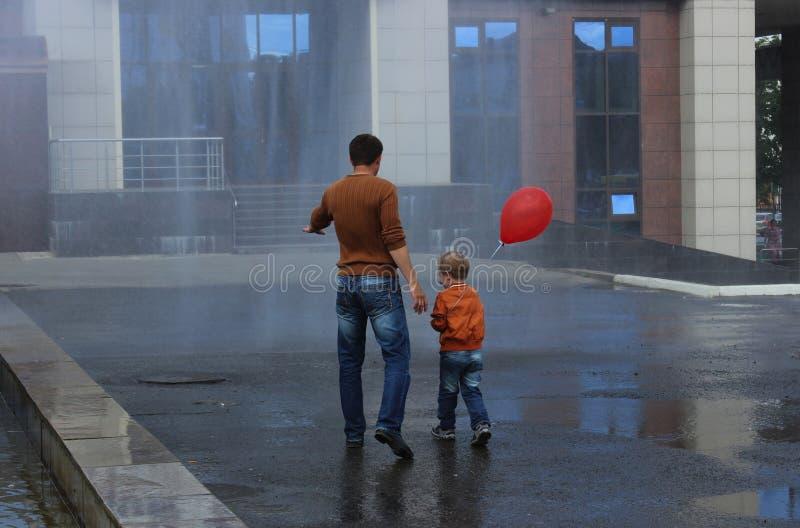 Fontanna deszczu syn i ojciec fotografia stock