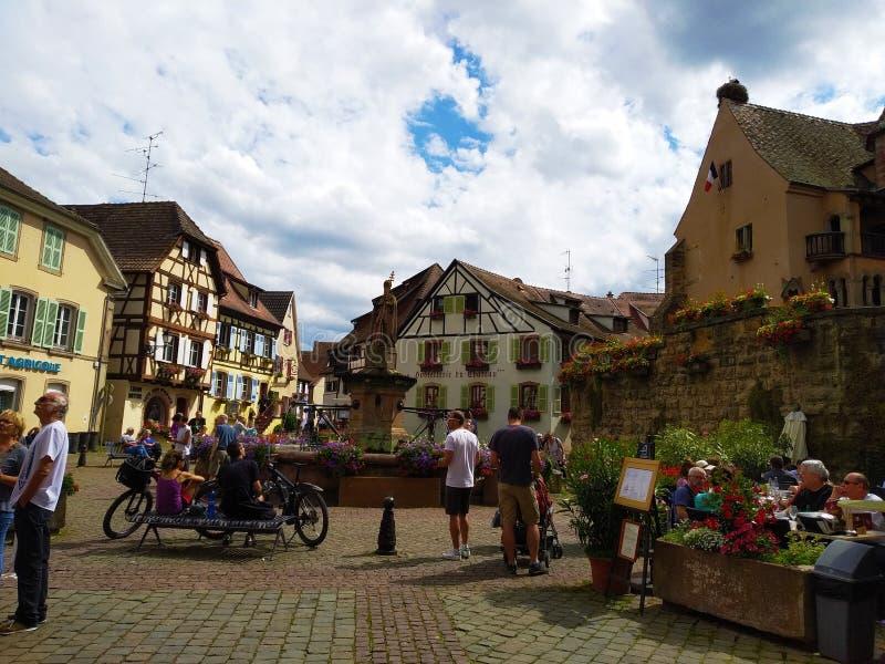 Fontanna w głównym placu Eguisheim otaczał typowymi domami Alsace fotografia royalty free