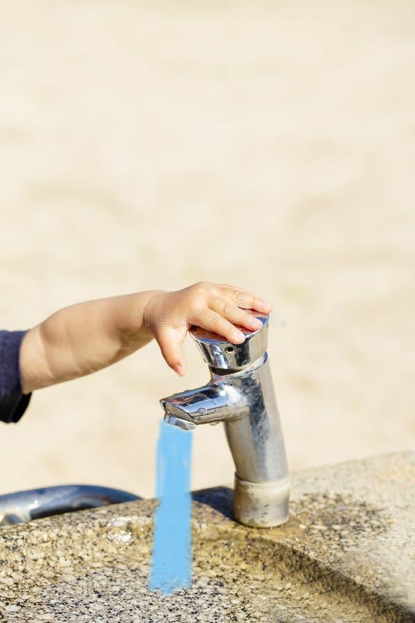 Fonte bebendo pública com mão pequena dos child's no parque da cidade foto de stock