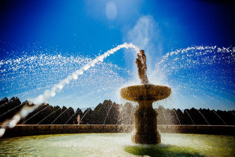 Fonte clássica com os jatos formando arcos da água e do céu azul fotografia de stock royalty free