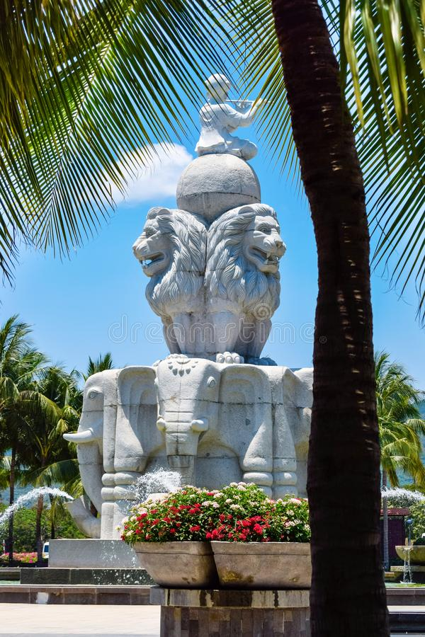 Fonte com as estátuas dos elefantes e dos leões no parque com flores e a palmeira tropicais fotografia de stock