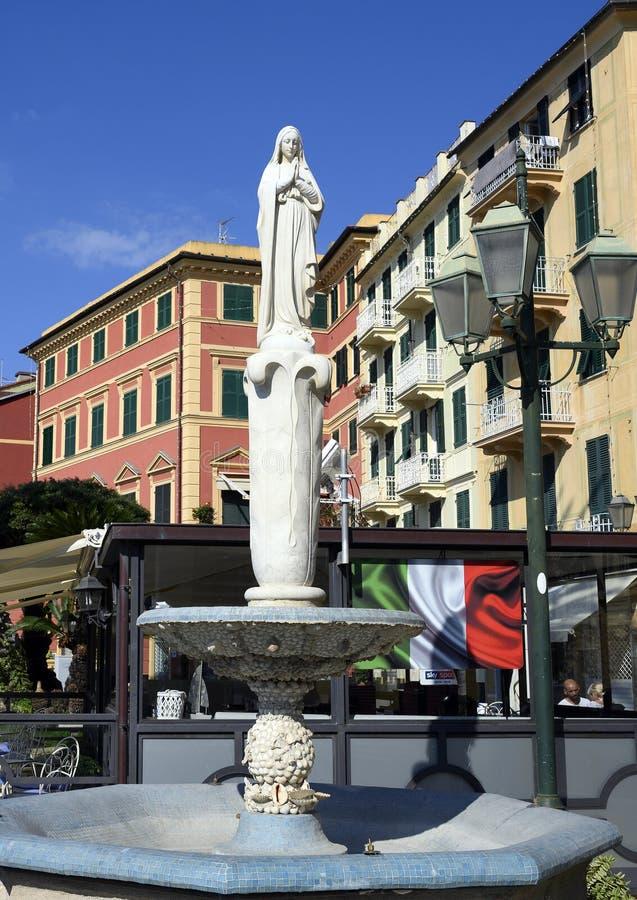 Fonte com a estátua de Santa Margherita de Antioch e da bandeira italiana no fundo fotografia de stock