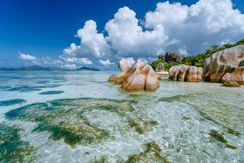 Fonte d'ansa d'argent su bassa marea - Paradise tropical Beach con laguna blu superficiale, massi graniti e nuvole bianche fotografia stock libera da diritti