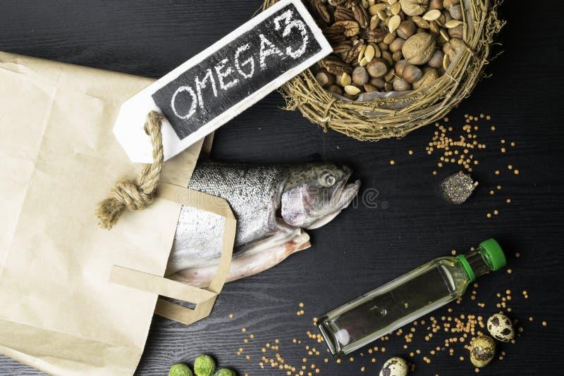 Fonte da ômega 3 Salmões ou truta gorda saudável, óleo, porcas, sementes, chia, lentilhas, couves de Bruxelas, ovos imagens de stock royalty free