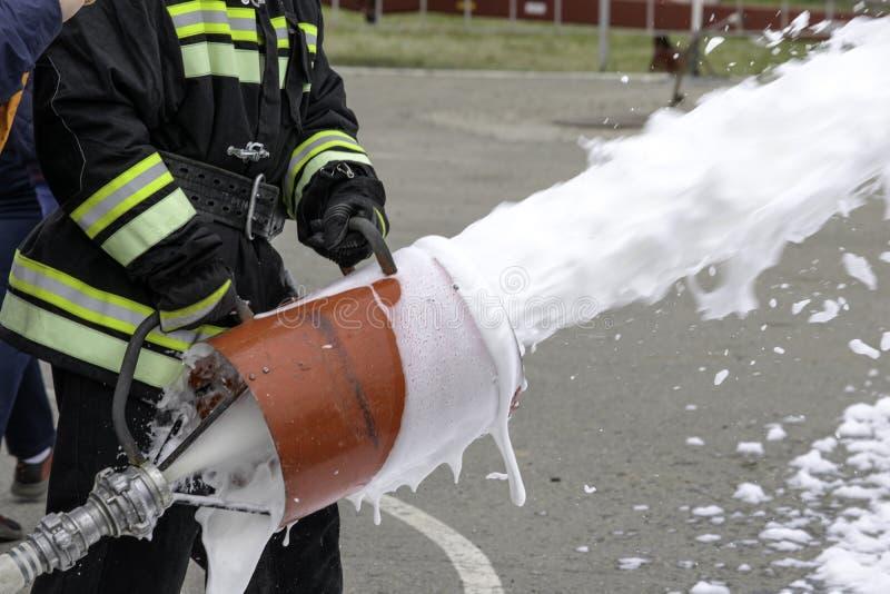Fonte da espuma de um gerador de espuma, fogo - extinguir a espuma voa do gerador de espuma, que mant?m o bombeiro no combate imagens de stock royalty free