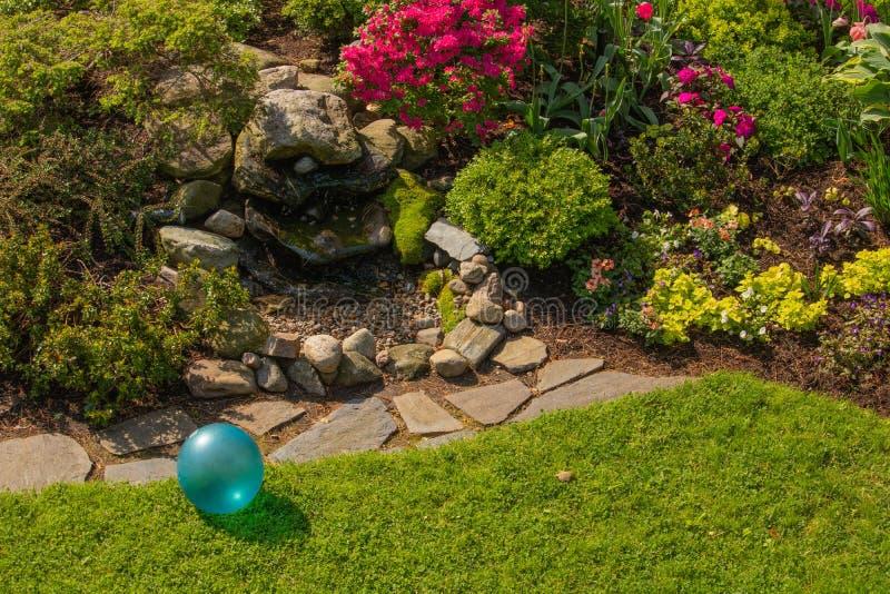 Fonte da pedra do jardim do quintal com a bola brilhante do brinquedo da infância do azul de turquesa na luz solar da mola imagens de stock