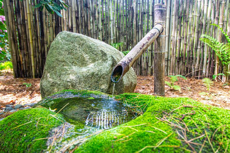 Fonte de água de bambu com bacia musgoso e rocha foto de stock