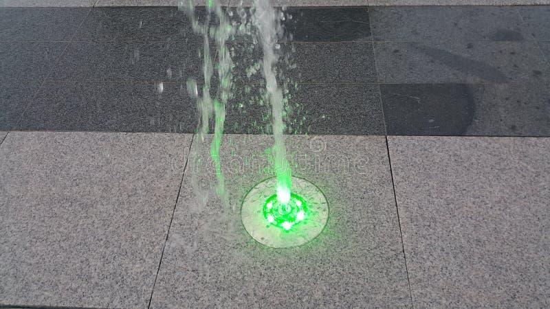 Fonte de água clara bonita e colorida sobre o assoalho concreto fotos de stock royalty free