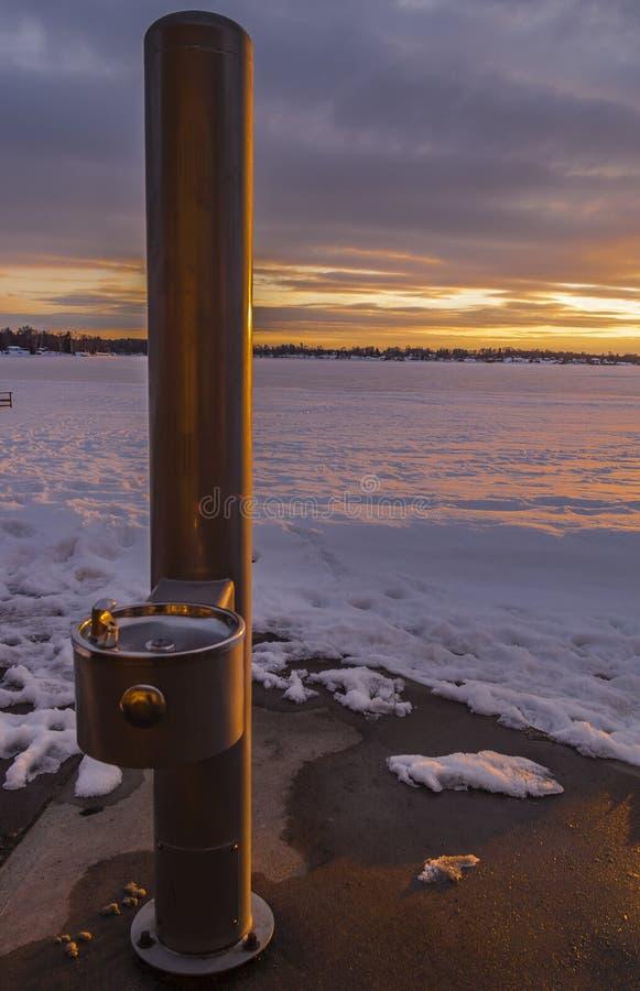 Fonte de água potável pelo lago congelado fotos de stock