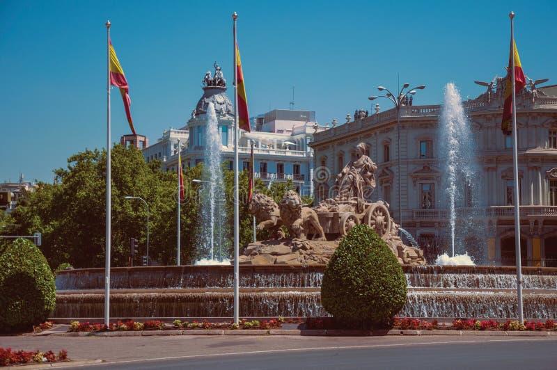 Fonte de Cybele com bandeiras espanholas e construções velhas no Madri foto de stock royalty free