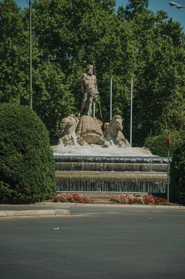 Fonte de Netuno entre árvores frondosas no Madri fotos de stock