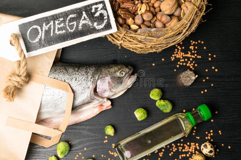 Fonte di Omega 3 Salmone o trota grasso sano, olio, dadi, semi, chia, lenticchie, cavolini di Bruxelles, uova immagini stock libere da diritti