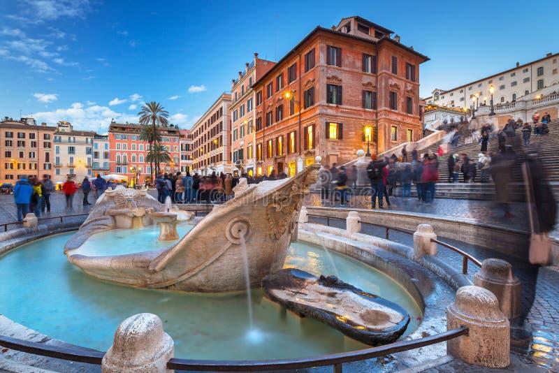 Fonte no quadrado de di Spagna da praça e nas etapas espanholas em Roma no crepúsculo, Itália imagem de stock