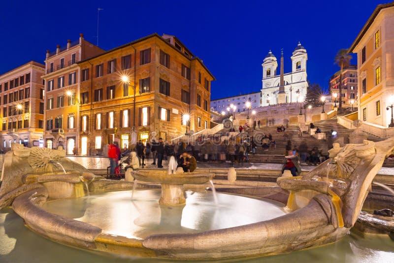Fonte no quadrado de di Spagna da praça e nas etapas espanholas em Roma na noite, Itália fotografia de stock