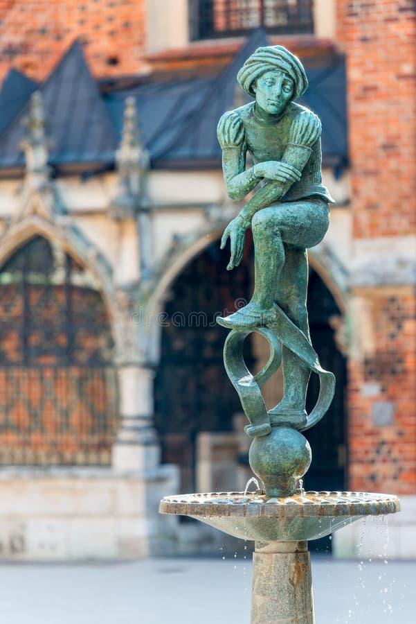 Fonte pobre do estudante de Jacques da escultura no centro de Krakow, foto de stock