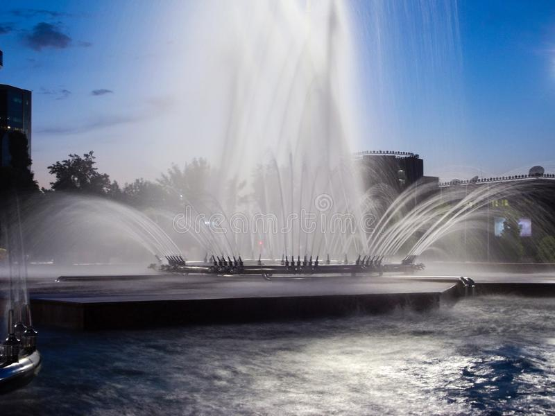 Fontein in de lichten van stad stock afbeeldingen