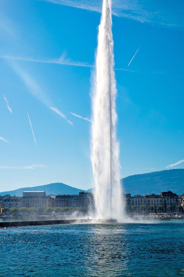 Fontein de straal van d'eau (Straal van Water) op Meer Genève met de stad in de achtergrond en vliegtuigslepen in de hemel stock fotografie