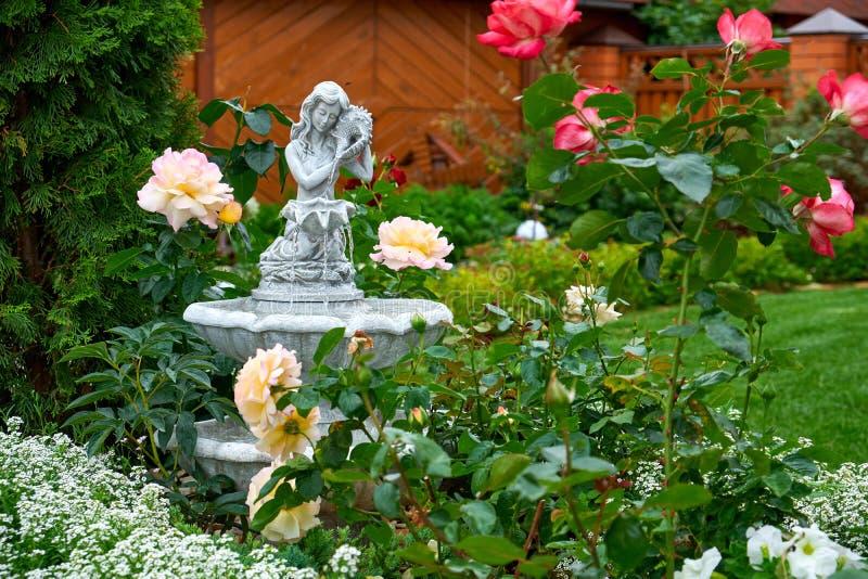 Fontein in de tuin Het ontwerp van het landschap Bloementuin Bloemen in de tuin na regen De zorg van tuininstallaties royalty-vrije stock afbeelding