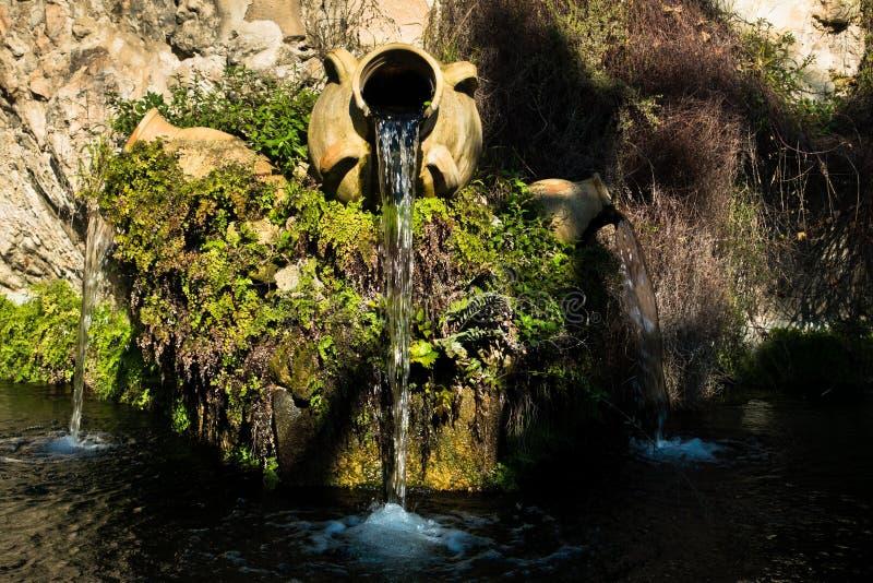 Fontein in een park met water die van oude amfora, Cagliari, Sardinige stromen stock afbeeldingen