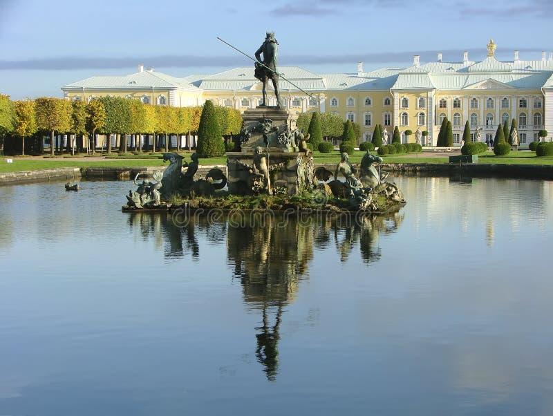 Fontein Neptunus op de achtergrond van het Paleis van Peterhof van de huisvestingszegel Grote Peterhof St Petersburg Rusland stock foto