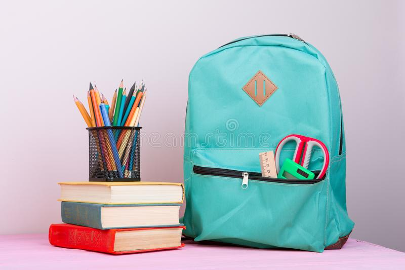 Fontes azuis da trouxa e de escola: o bloco de notas, livros, tesouras, penas, lápis, régua, calculadora está na tabela de madeir imagens de stock royalty free