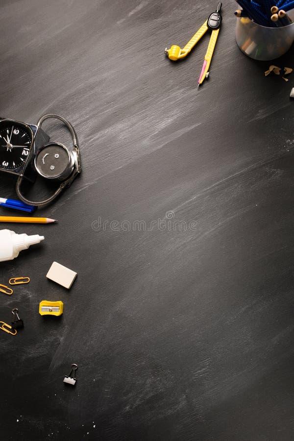 Fontes de escola, alarme, lápis na opinião superior do quadro preto, espaço da cópia, moldação vertical Conceito: de volta à esco imagens de stock