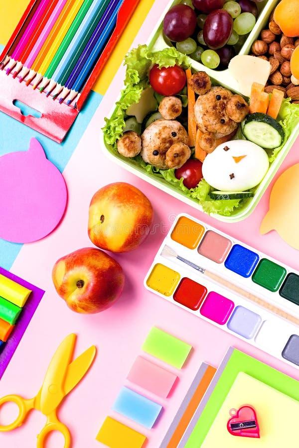 Fontes de escola, artigos de papelaria coloridos, trouxa e cesta de comida com alimento engraçado para crianças De volta ao conce foto de stock royalty free