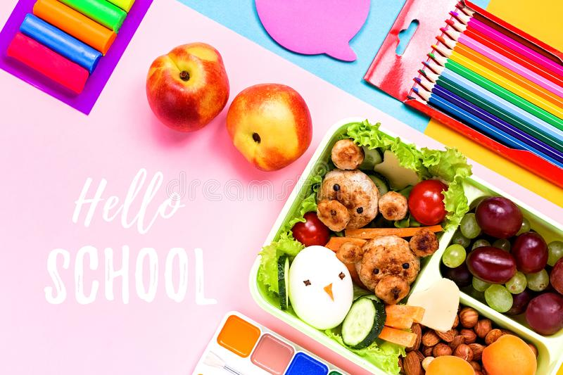 Fontes de escola, artigos de papelaria coloridos, trouxa e cesta de comida com alimento engraçado para crianças De volta ao conce foto de stock