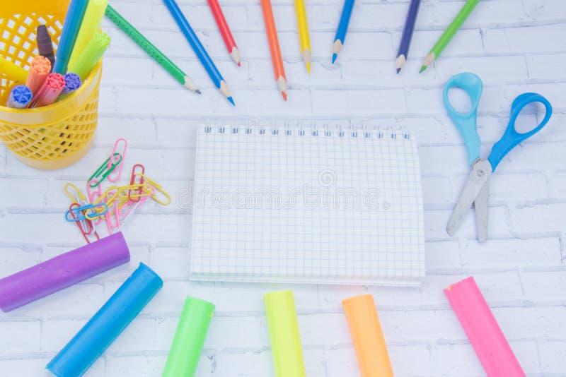 Fontes de escola Colora lápis, livro de nota, penas azuis, sciccors, marcadores, colagem, apontador, grampos foto de stock