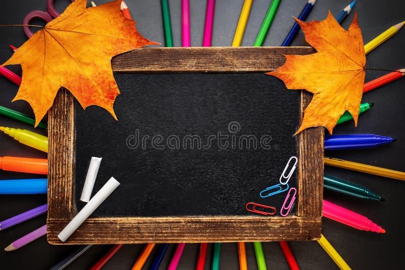 Fontes de escola com artigos de papelaria e quadro com os l?pis coloridos no fundo preto da placa De volta ? escola Configura??o  fotografia de stock