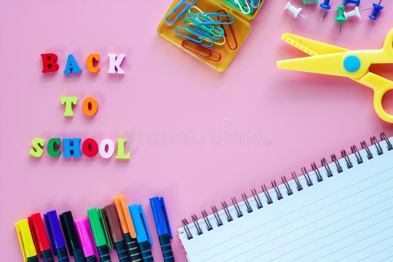 Fontes de escola com texto de madeira DE VOLTA À ESCOLA no backgrou cor-de-rosa fotografia de stock