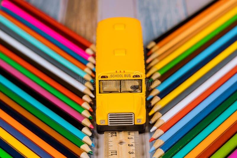 Fontes de escola, lápis coloridos e ônibus do estudante do brinquedo Conceito da instru??o imagem de stock