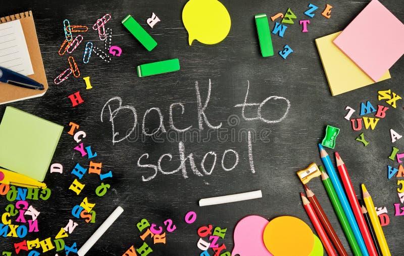 fontes de escola: lápis de madeira coloridos, caderno, etiquetas de papel, clipes de papel, apontador e inscrição branca do giz foto de stock royalty free