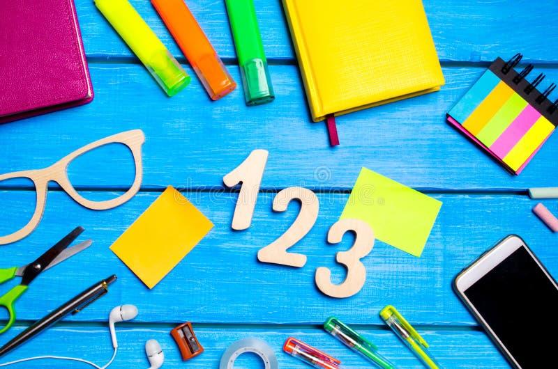 Fontes de escola na mesa da escola, artigos de papelaria, conceito da escola, fundo azul, caos criativo, espaço para o texto, mar fotos de stock