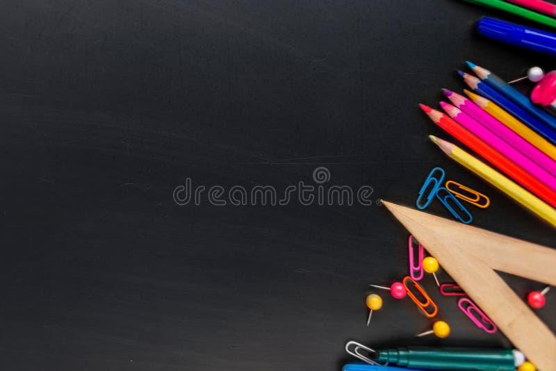 Fontes de escola no fundo preto da placa com artigos de papelaria De volta ? escola, conceito do escrit?rio Configura??o lisa, co fotografia de stock