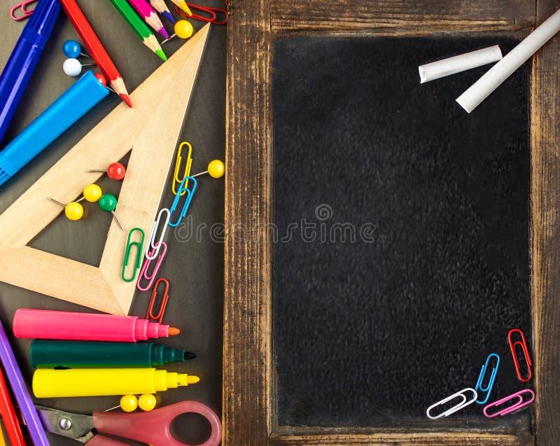 Fontes de escola no fundo preto da placa com artigos de papelaria De volta ? escola, conceito do escrit?rio Configura??o lisa, co imagem de stock royalty free