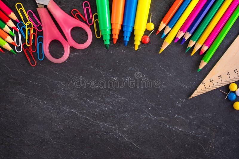 Fontes de escola no fundo preto da placa de giz, vista superior back foto de stock