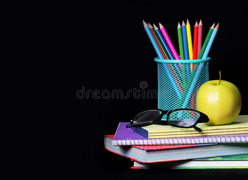 Fontes de escola sobre o preto Uma maçã, lápis coloridos imagem de stock