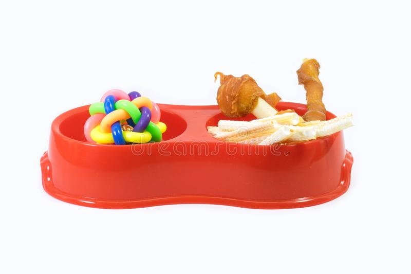 Fontes do animal de estimação sobre a bacia plástica com petiscos e os brinquedos de borracha para imagens de stock royalty free