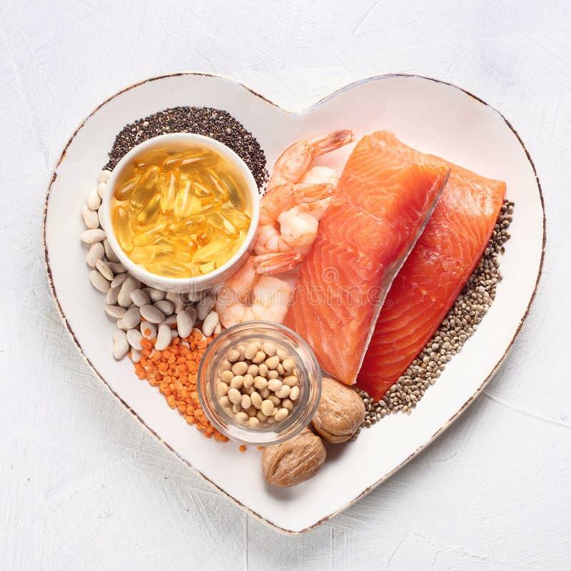 Fonti di Omega 3 in piatto di forma del cuore immagine stock