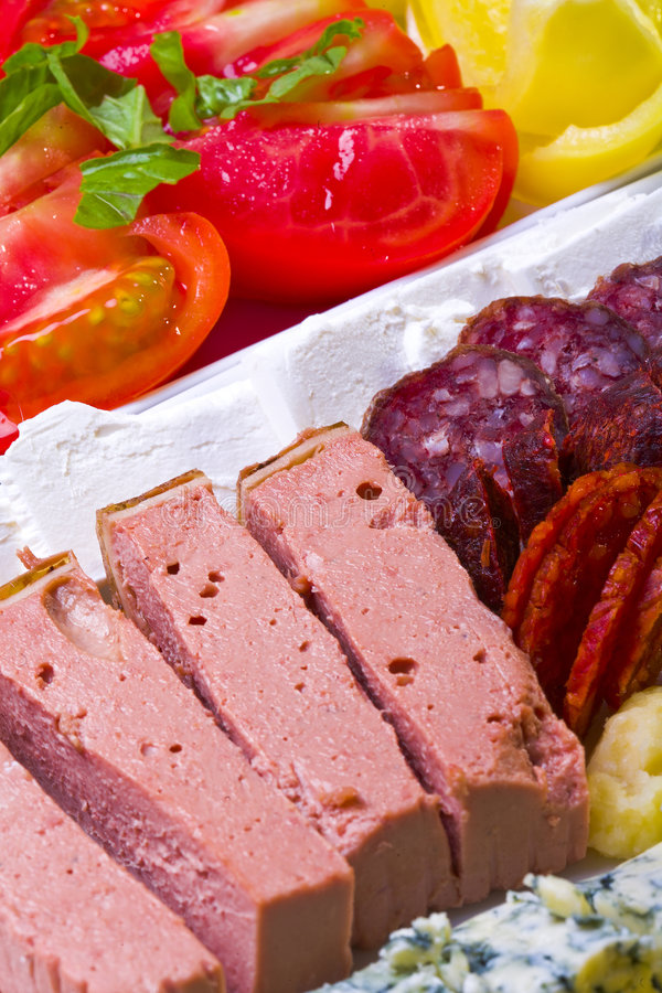 Food. Gourmet food arrangement with foie-gras,salami,sausages,blue cheese and vegetables stock photo