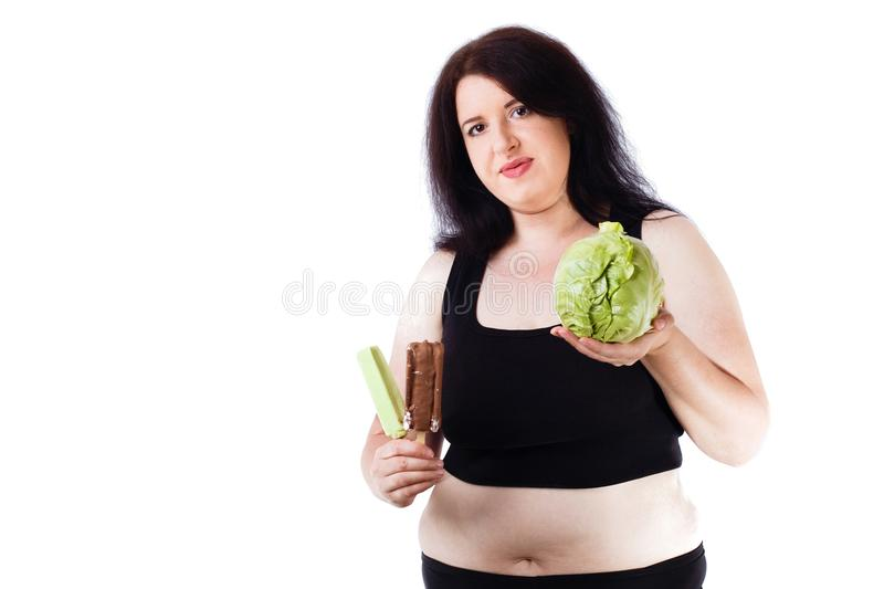 Young overweight food addicted woman choosing between junk and h stock image