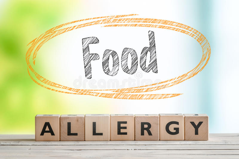 Food allergy sign on a table. With a nature background stock photos