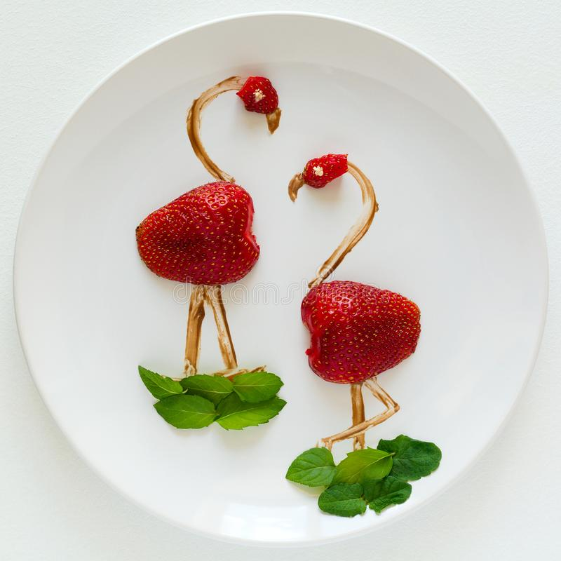 Food art creative concept. Flamingos on white plate. Strawberry, chocolate and mint composition stock photo
